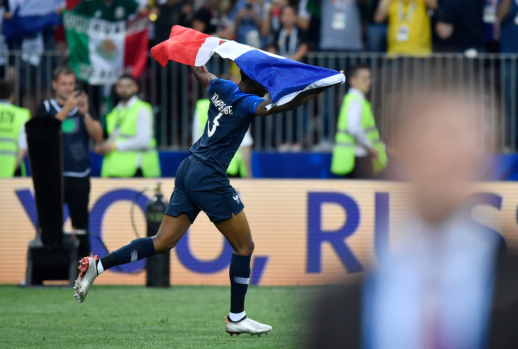 . France\'s Presnel Kimpembe celebrates with his country\'s flag after winning 4-2 during the final match between France and Croatia at the 2018 soccer World Cup in the Luzhniki Stadium in Moscow, Russia, Sunday, July 15, 2018. (AP Photo/Martin Meissner)