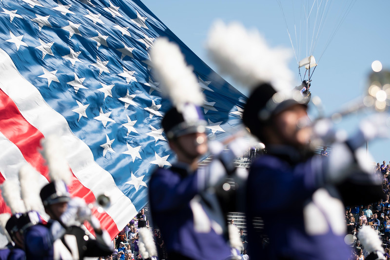 A parachuter carrying the Star Spangled Banner lands behind the Northwestern Marching band before a football game on Saturday, September 14, 2019. | Colin Boyle/Northwestern Athletics