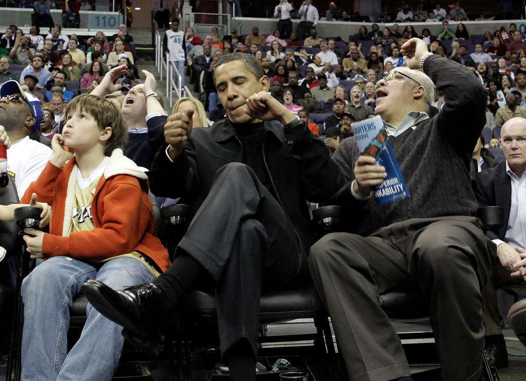 . Chicago Bulls fan President Barack Obama, center, reacts to a Bulls three-pointer against the Washington Wizards during the fourth quarter of an NBA basketball game on Friday, Feb.  27, 2009 in Washington.  (AP Photo/Evan Vucci)