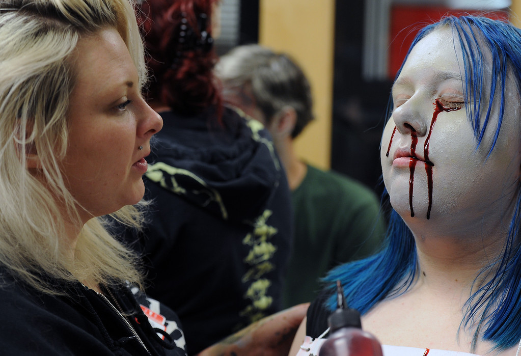 """. BOULDER, CO- FEBRUARY 19:  \""""Zombie\"""" Zoe Lloyd-Carpenter, 14, looks transformed by her make-up.  Make-up artist Danica Hughes, of Theatrical Costumes, Etc., applies blood that drips down her face.   With the help of a professional videographer, Fairview High School students produced a zombie video to advertise an Awareness Drive in Boulder Valley schools designed to bring attention to a variety of mental health and wellness issues.  Students were made to look like zombies by make-up artists from Theatrical Costumes, Etc. (Photo By Helen H. Richardson/ The Denver Post)"""