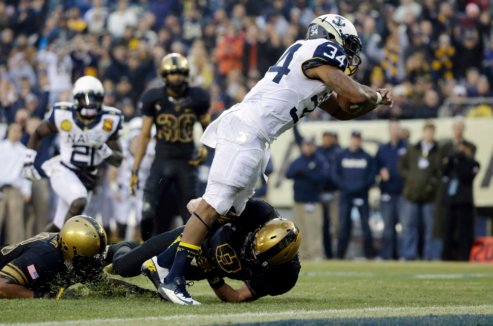 . Navy\'s Noah Copeland (34) rushes for a touchdown as Army\'s Hayden Pierce (9) hangs on during the first half of an NCAA college football game, Saturday, Dec. 8, 2012, in Philadelphia. (AP Photo/Matt Slocum)