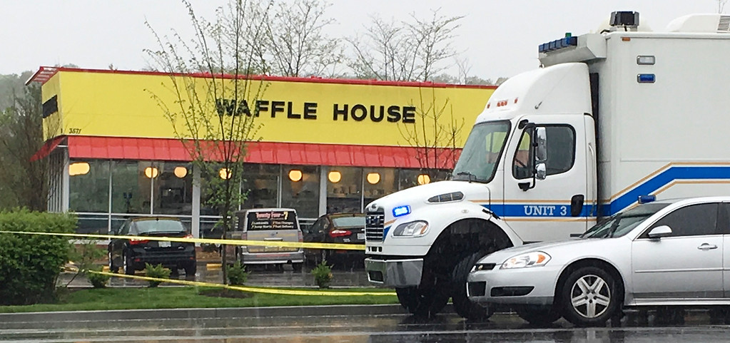 . Police vehicles sit outside a Waffle House restaurant in Nashville, Tenn., Sunday, April 22, 2018. A man stormed the Waffle House restaurant in Tennessee before dawn Sunday and shot several people to death, according to police, who credited a customer with saving lives by wresting a weapon away from the gunman. (AP Photo/Sheila Burke)