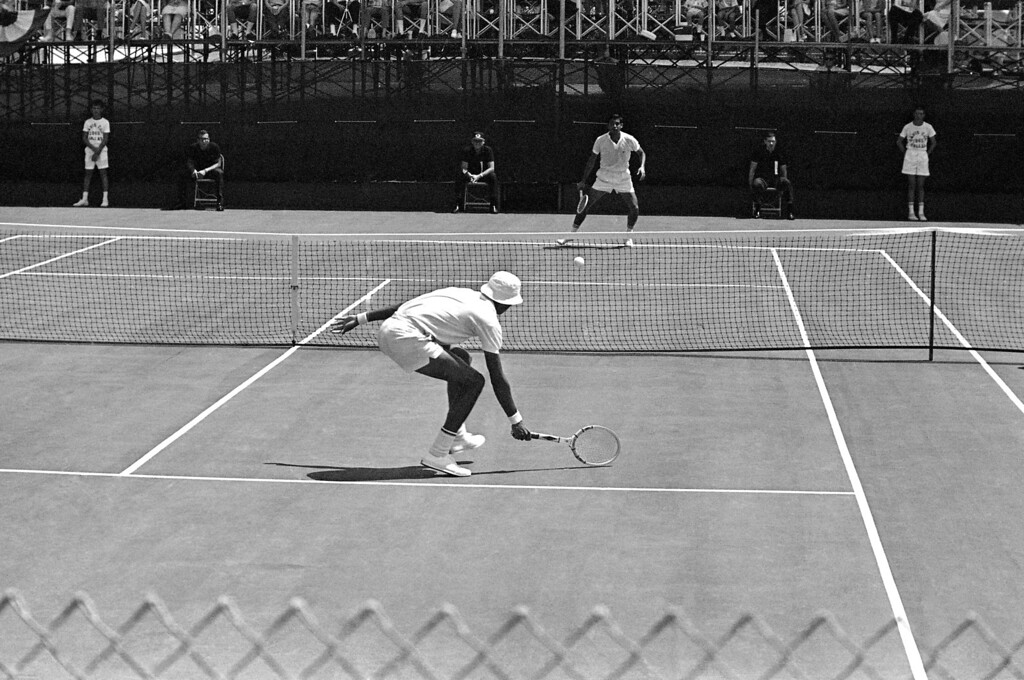 . Arthur Ashe, foreground, U.S. Davis cup player, sends the ball into the net on a return to Rafael Ozuna in the opening singles match of the American Zone finals between Mexico and U.S. in Dallas, Texas on July 31, 1965. (AP Photo/Ferd Kaufman)