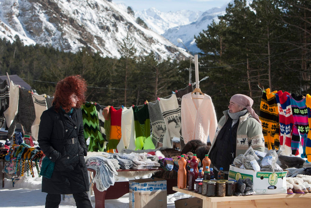 . A woman (R) sells memorable gifts, clothes and other goods near a ski slope of Mount Elbrus, February 3, 2013. These days only a handful of the most intrepid skiers and hikers make it to Elbrus, which dominates the North Caucasus region, where Islamist insurgents from ethnic minorities are fighting Russian rule and want to establish an Emirate. Elbrus is the unlikely centerpiece of a $26-billion Kremlin project for a chain of luxury mountain resorts that Moscow hopes will succeed, where guns and troops have not, in ending the violence and easing dissent in the region. Picture taken February 3, 2013. REUTERS/Kazbek Basayev