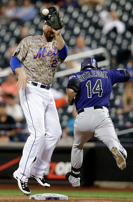 . Colorado Rockies Josh Rutledge (14) is safe at first legging out a first inning single as New York Mets first baseman Lucas Duda (21) fields the throw in a baseball game in New York, Monday, Sept. 8, 2014. (AP Photo/Kathy Willens)