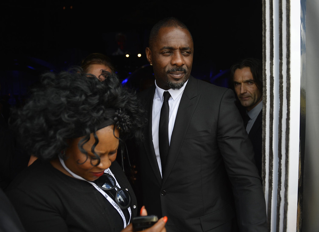 . British actor Idris Elba, center, leaves following former South African President Nelson Mandela\'s funeral service in Qunu, South Africa, Sunday, Dec. 15, 2013. (AP Photo/Odd Andersen, Pool)