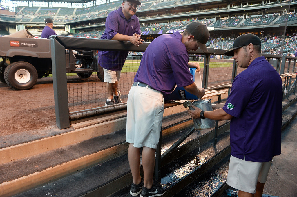 . DENVER, CO. - AUGUST 16:  Colorado Rockies grounds crew fill up a watering with ice water from the Cincinnati Reds dugout to water down home plate at Coors Field Saturday evening, August 16, 2014. The Rockies were set to play the Cincinnati Reds but the game was cancelled due to a water main break along Blake St, out in front of Coors Field, cutting off water supply to the stadium. (Photo By Andy Cross / The Denver Post)