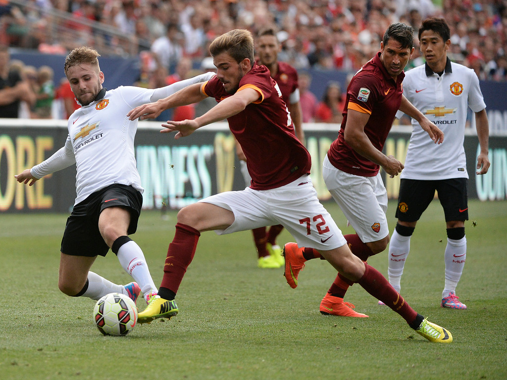 . AS Roma midfielder Mihai Balasa (72) lunged for the ball past Manchester United defender Luke Shaw, left, in the second half. Manchester United defeated AS Roma 3-2 in an exhibition soccer game at Sports Authority Field in Denver Saturday afternoon, July 27, 2014. Photo by Karl Gehring/The Denver Post