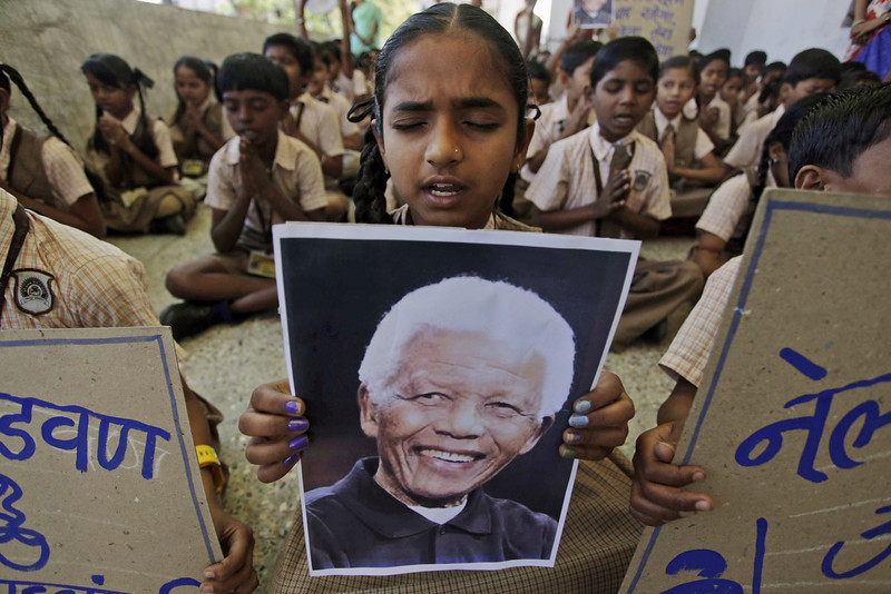 . A young Indian school girl holds a portrait of former South African president Nelson Mandela as she prays along with others on hearing of his death, at a school in Ahmadabad, India, Friday, Dec. 6, 2013. Mandela, South Africa\'s first black president, died Thursday in Johannesburg, South Africa after a long illness. He was 95. (AP Photo/Ajit Solanki)