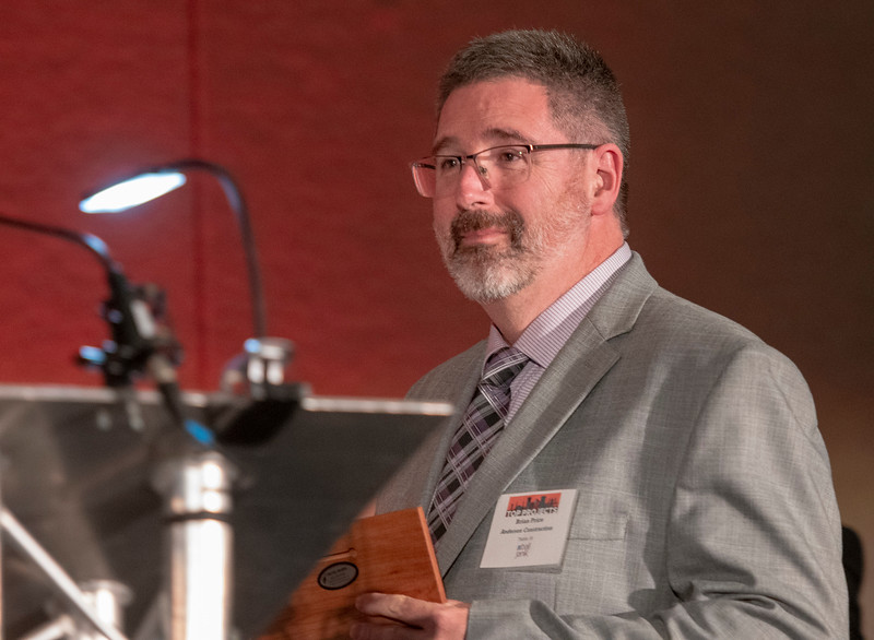 Brian Price of Andersen Construction accepts the third place award in the education renovation category for the company's work on the Southern Oregon University Lithia Pavilion. (Josh Kulla/DJC)