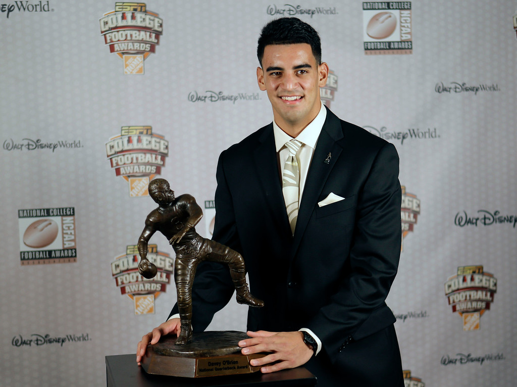 . Oregon\'s Marcus Mariota stands with his trophy after being awarded the Davey O\'Brien Award for Nation\'s Best Quarterback at the College Football Awards, Thursday, Dec. 11, 2014, in Lake Buena Vista, Fla. (AP Photo/John Raoux)