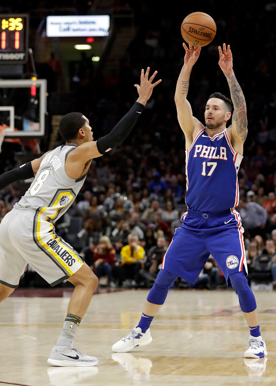 . Philadelphia 76ers\' JJ Redick (17) passes over Cleveland Cavaliers\' Jordan Clarkson (8) in the second half of an NBA basketball game, Thursday, March 1, 2018, in Cleveland. (AP Photo/Tony Dejak)