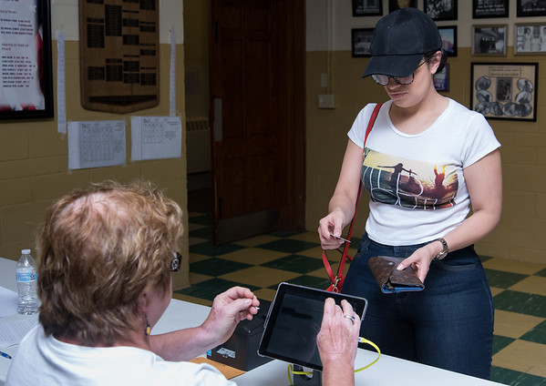 08/14/18 Wesley Bunnell | Staff Official Checker Izabella Szczepanski checks in Niomi Figueroa at the St. Francis of Assisi Church Hall voting location on Tuesday afternoon.