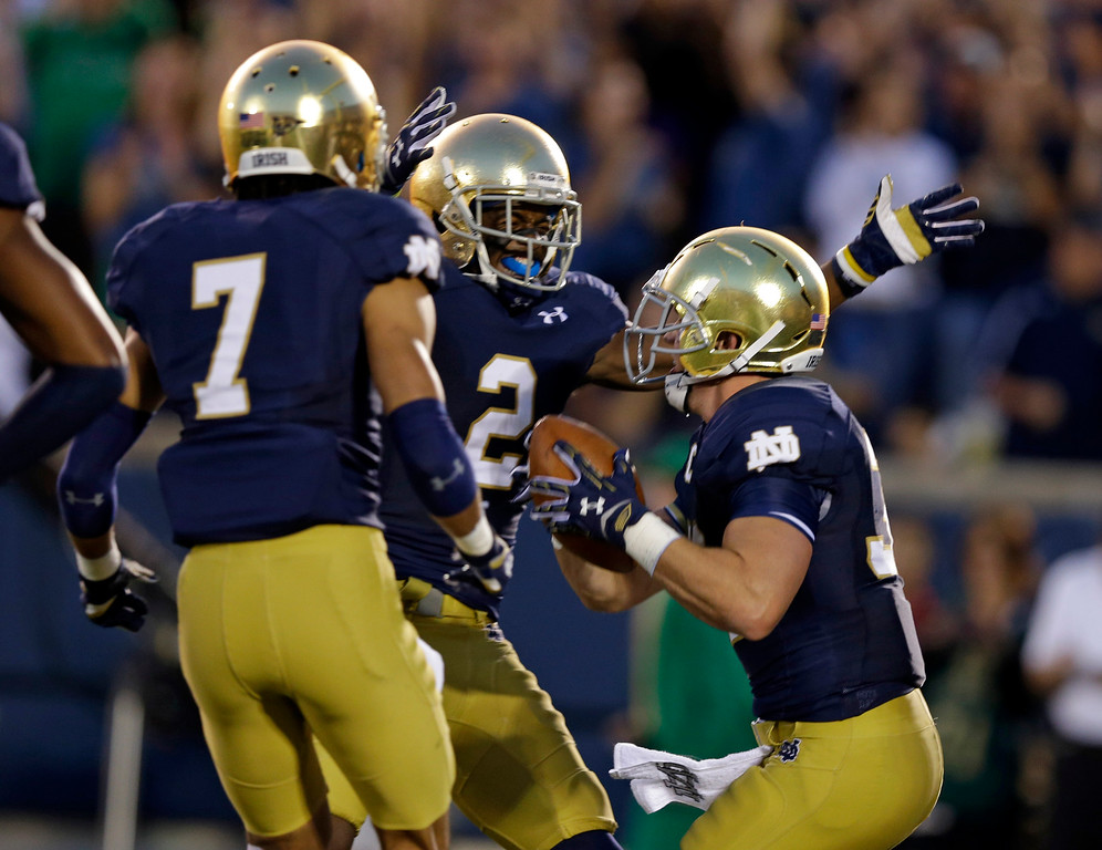 . Notre Dame running back Cam McDaniel celebrates after scoring a touchdown against Michigan with receivers Chris Brown (2) and William Fuller during the first half of an NCAA college football game in South Bend, Ind., Saturday, Sept. 6, 2014. (AP Photo/Michael Conroy)