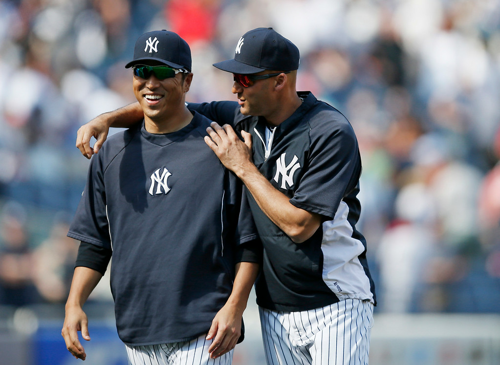 . New York Yankees Derek Jeter (2) walks off the field with New York Yankees starting pitcher Hiroki Kuroda, after the Yankees 1-0 defeat of the Detroit Tigers in a baseball game at Yankee Stadium in New York, Thursday, Aug. 7, 2014.  Both players watched the game from the dugout. (AP Photo/Kathy Willens)