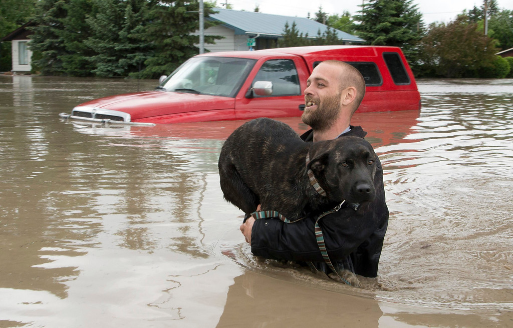 . A man carries his dog to safety in High River in Alberta province June 20, 2013. A state of emergency has been issued for the town of High River, which is being evacuated due to floods. REUTERS/Mike Sturk