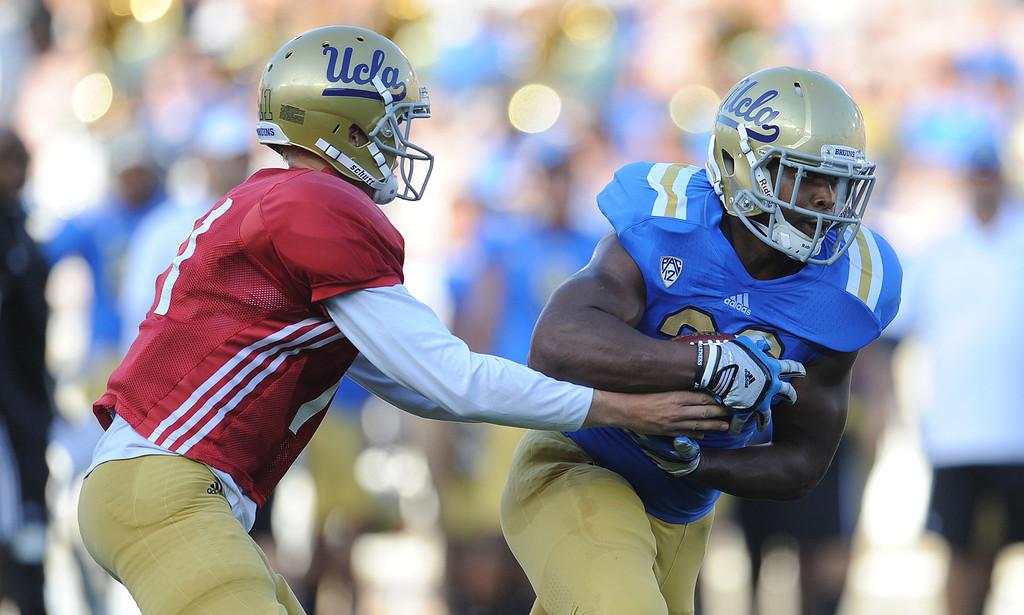 . UCLA quarterback Jerry Neuheisel (11) hands-off to running back Malcolm Jones (28) during the football spring showcase college football game in the Rose Bowl on Saturday, April 27, 2013 in Pasadena, Calif.    (Keith Birmingham Pasadena Star-News)
