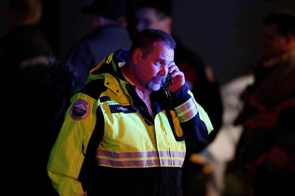 . A paramedic talks on the phone outside Clackamas Town Center in Clackamas, Ore., where a shooting occurred Tuesday, Dec. 11, 2012. A gunman opened fire in the Portland, Ore., area shopping mall Tuesday, killing at least one person and wounding an unknown number of others, sheriff\'s deputies said. (AP Photo/The Oregonian, Bruce Ely)