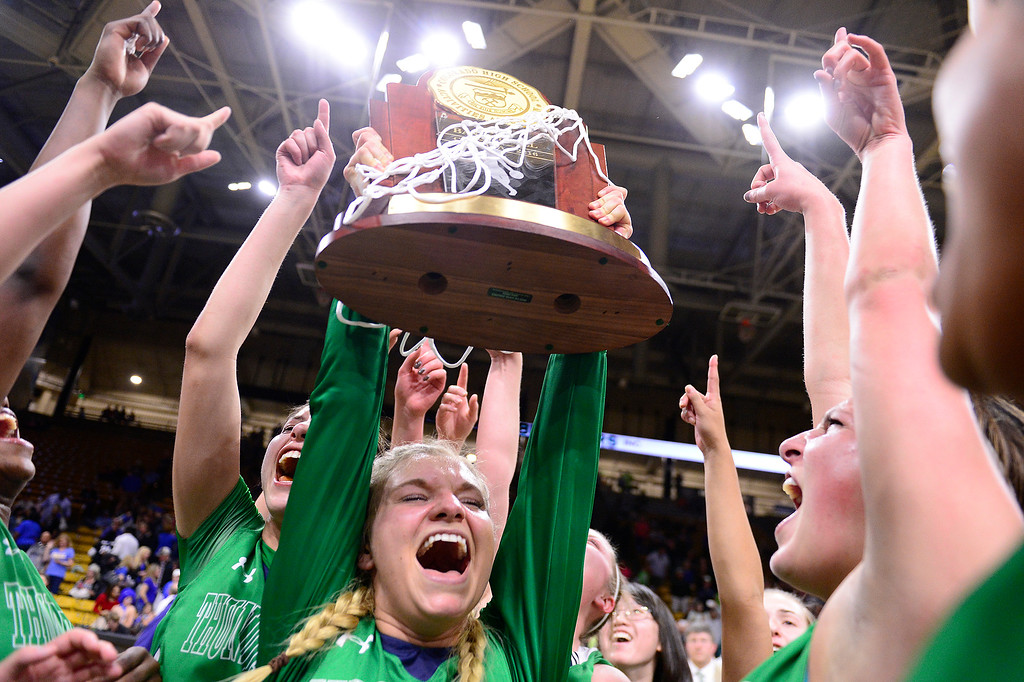 . ThunderRidge players raise the trophy into the air as they celebrate at the Coors Events Center on March 12, 2016 in Boulder, Colorado. ThunderRidge defeated Highlands Ranch 47-32 to win the Class 5A Colorado State Basketball Championship. (Photo by Brent Lewis/The Denver Post)