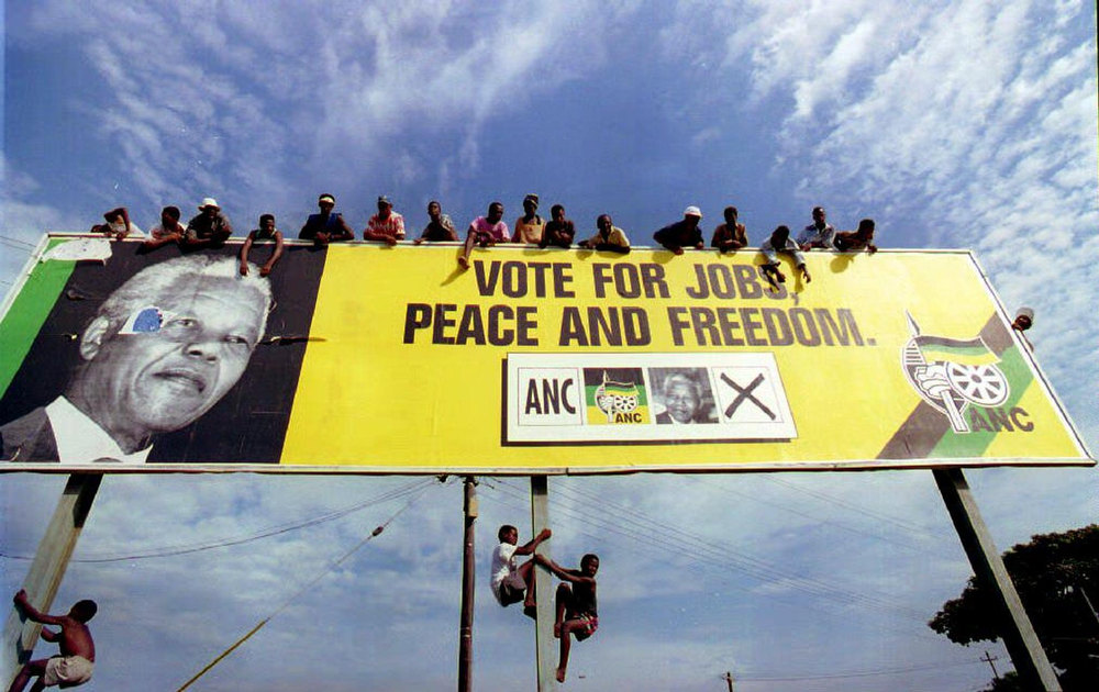 Description of . A picture taken 16 April 1994 shows African National Congress supporters waiting for Nelson Mandela on a billboard in a township just outside Durban before for a pre-election rally in Natal/KwaZulu province. South Africa held its first non-racial elections in 1994, ending more than three centuries of white domination and 46 years of apartheid rule. (Photo credit should read ALEXANDER JOE/AFP/Getty Images)