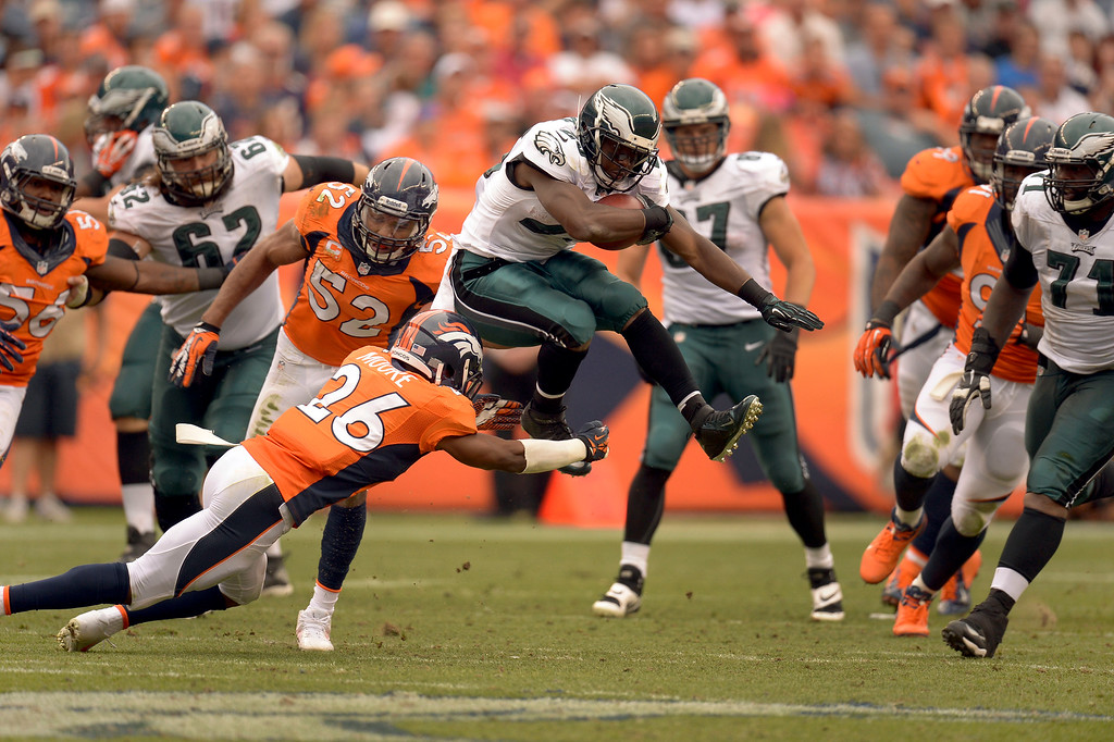 . Philadelphia Eagles running back LeSean McCoy (25) leaps over Denver Broncos free safety Rahim Moore (26) for a short gain during the third quarterSeptember 29, 2013 at Sports Authority Field at Mile High in Denver . (Photo by John Leyba/The Denver Post)
