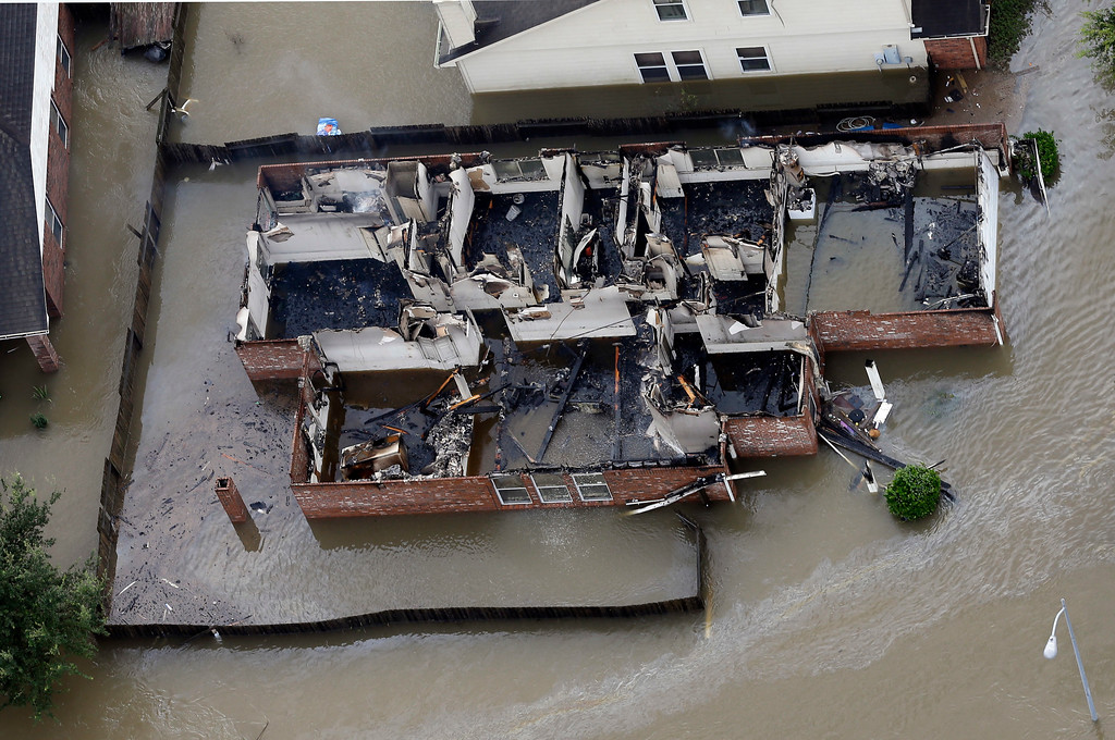 . A burned out home is surrounded by floodwaters from Tropical Storm Harvey, Tuesday, Aug. 29, 2017, in Spring, Texas. (AP Photo/David J. Phillip)