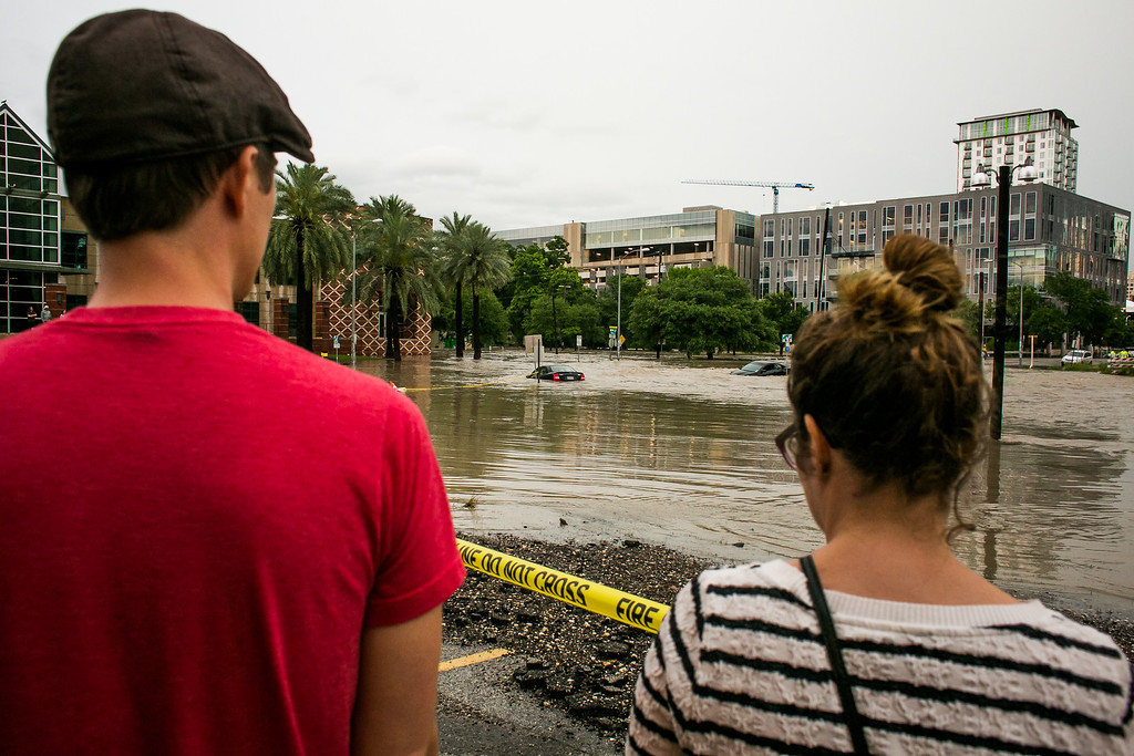 . AUSTIN, TX - MAY 25:   A couple watches flooding at Shoal Creek after days of heavy rain on May 25, 2015 in Austin, Texas. Texas Gov. Greg Abbott toured the damage zone where one person is confirmed dead and at least 12 others missing in flooding along the Rio Blanco, which reports say rose as much as 40 feet in places, caused by more than 10 inches of rain over a four-day period. The governor earlier declared a state of emergency in 24 Texas counties.  (Photo by Drew Anthony Smith/Getty Images)