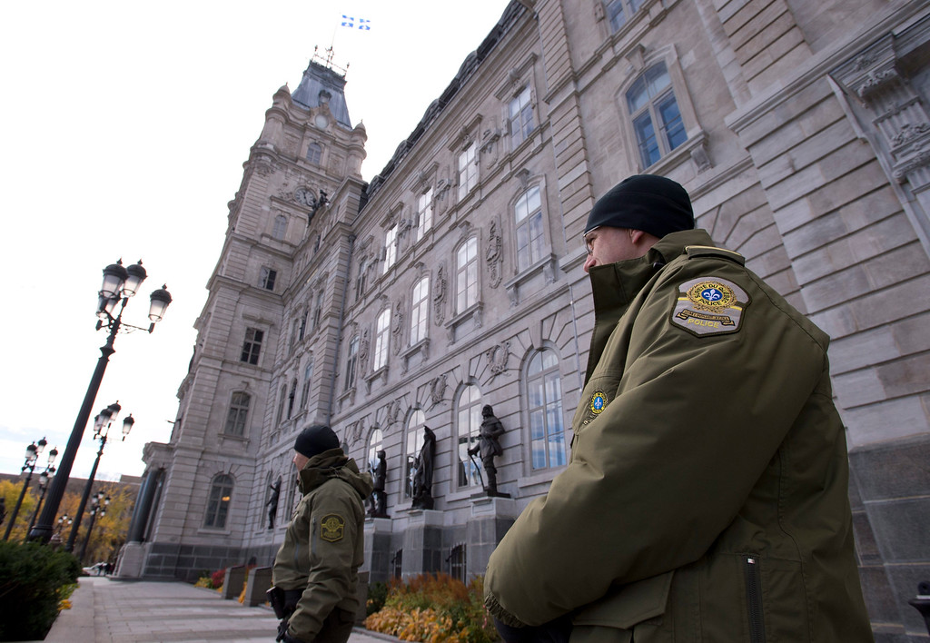 . Surete du Quebec stand guard at the National Assembly in Quebec City after a gunman opened fire in Ottawa on Wednesday Oct. 22, 2014.  A soldier standing guard at the National War Memorial was shot by an unknown gunman and people reported hearing gunfire inside the halls of Parliament. Prime Minister Stephen Harper was rushed away from Parliament Hill to an undisclosed location, according to officials. (AP Photo/The Canadian Press,  Jacques Boissinot)