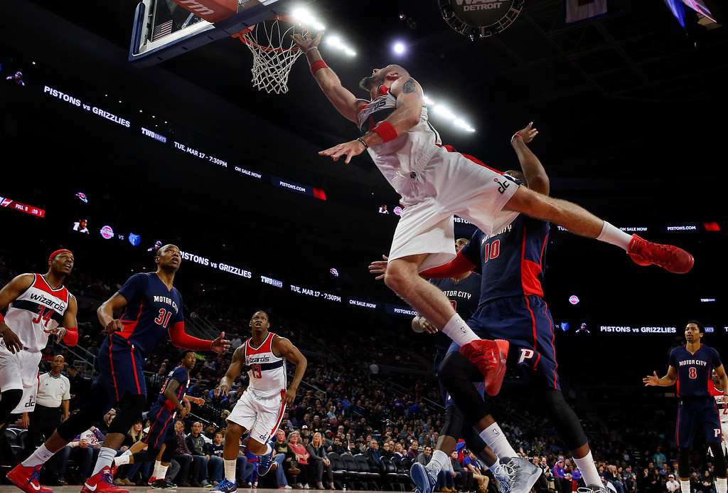 . Washington Wizards center Marcin Gortat, foreground, drives against the Detroit Pistons in the second half of an NBA basketball game in Auburn Hills, Mich., Sunday, Feb. 22, 2015. (AP Photo/Paul Sancya)