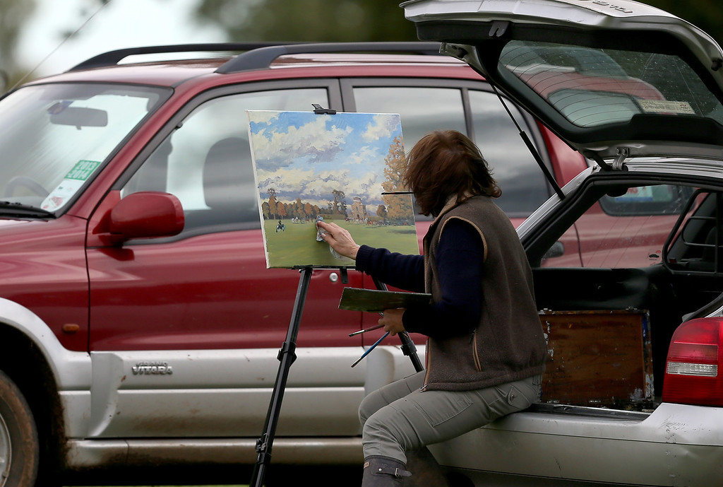 . BADMINTON, GLOUCESTERSHIRE - NOVEMBER 02:  A woman paints as riders from the Duke of Beaufort\'s Hunt arrive with the hounds for their opening meet of the season at Worcester Lodge on November 2, 2013 near Badminton in Gloucestershire, England. Traditionally the hunting season starts at the beginning of November and although a ban on fox hunting with dogs has been in force since February 2005, many supporters of fox hunting are continuing to call for a repeal of the ban, saying the current law is hard to interpret and enforce.  (Photo by Matt Cardy/Getty Images)