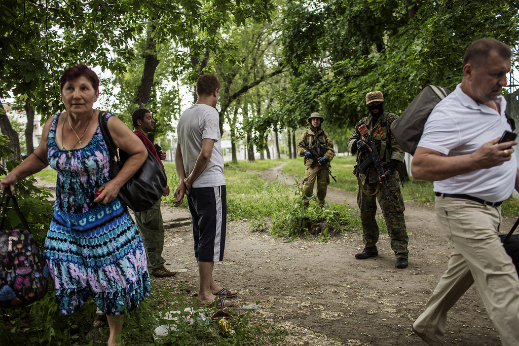 . Men stand next to armed pro-Russian militants as a woman runs away during clashes with Ukrainian forces near the airport in Donetsk on May 26, 2014. The battle at the airport in the main eastern rebel-held city of Donetsk on Monday marked a dramatic new phase in the government\'s offensive against pro-Russian separatists. The fierce confrontation erupted after Ukrainian oligarch Petro Poroshenko, who claimed victory in Sunday\'s crucial presidential election, vowed he would not let the separatists turn the east into another Somalia.  FABIO BUCCIARELLI/AFP/Getty Images