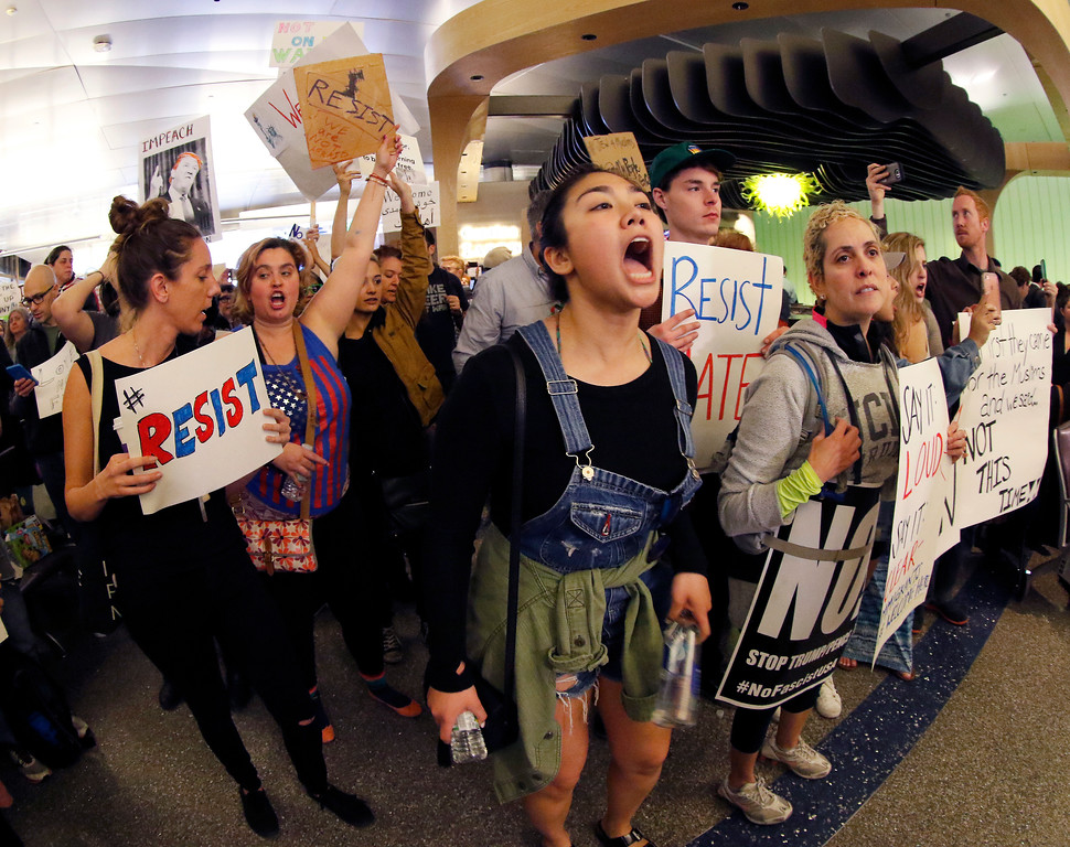 . Demonstrators chant inside Tom Bradley International Terminal as protests against President Donald Trump\'s executive order banning travel from seven Muslim-majority countries continue at Los Angeles International Airport Sunday, Jan. 29, 2017. (AP Photo/Ryan Kang)