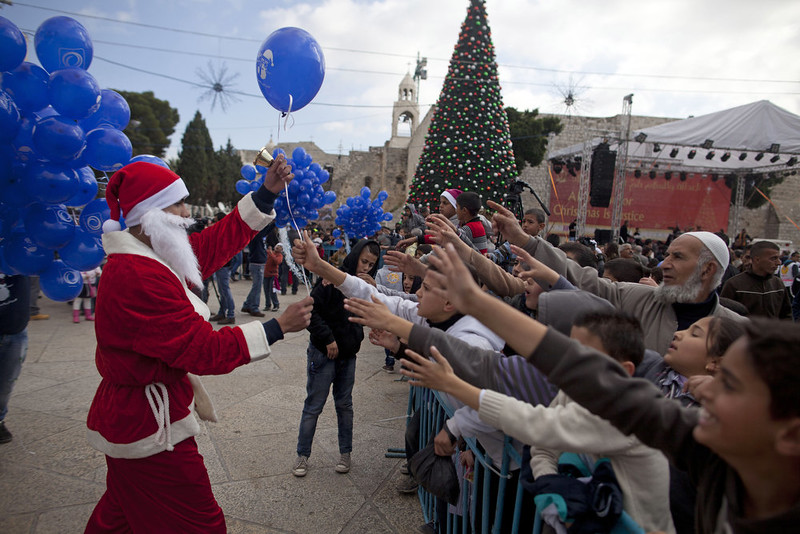. A Palestinian man dressed in a Santa Claus costume gives out balloons outside the Church of the Nativity on December 24, 2014 in Bethlehem, West Bank. Every Christmas pilgrims travel to the church where a gold star embedded in the floor marks the spot where Jesus was believed to have been born.  (Photo by Lior Mizrahi/Getty Images)