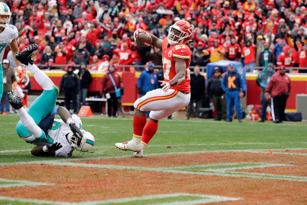. Kansas City Chiefs running back Kareem Hunt (27) scores a touchdown away Miami Dolphins linebacker Lawrence Timmons (94) from during the first half of an NFL football game in Kansas City, Mo., Sunday, Dec. 24, 2017. (AP Photo/Charlie Riedel)