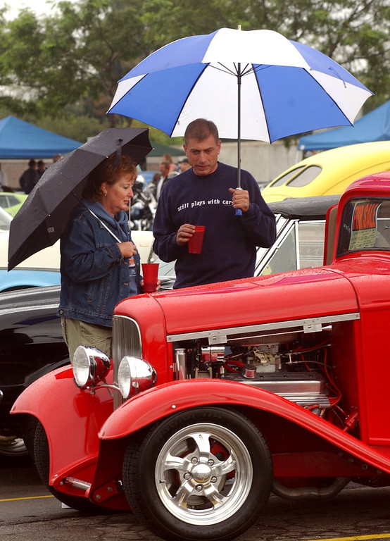 . Chris Napper,right, of Sterling Heights with his freidn Karen Kailer of Chicago checkout a classic 1932 3-window Ford Coup on display in the parking lot of the Phoneix Plaza in downtown Pontiac during Friday night\'s Woodward Dream Cruise. The annual classic cruise goes from Pontiac to Ferndale covering 16-miles of classic cars, food & entertainment along the way.