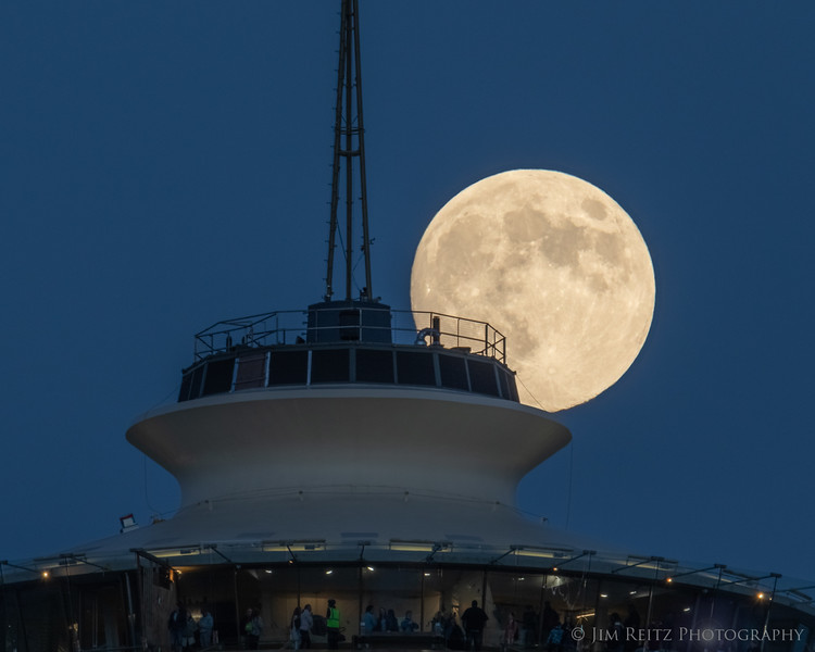Full moon rising behind the Space Needle's observation deck.