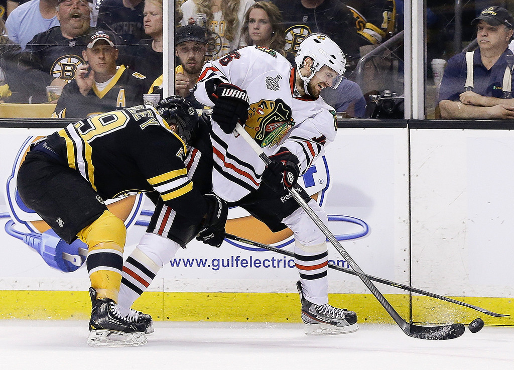 . Boston Bruins center Rich Peverley (49) checks Chicago Blackhawks center Marcus Kruger (16) during the second period in Game 6 of the NHL hockey Stanley Cup Finals Monday, June 24, 2013 in Boston. (AP Photo/Elise Amendola)
