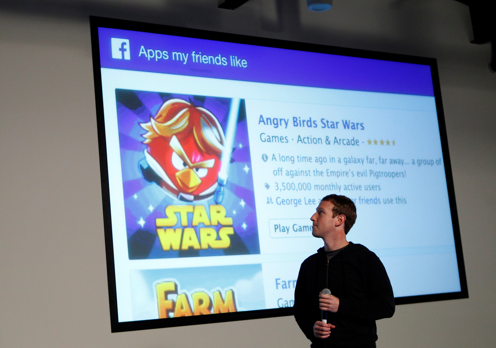 Description of . Facebook Chief Executive Mark Zuckerberg looks at the screen as he introduces a new feature called