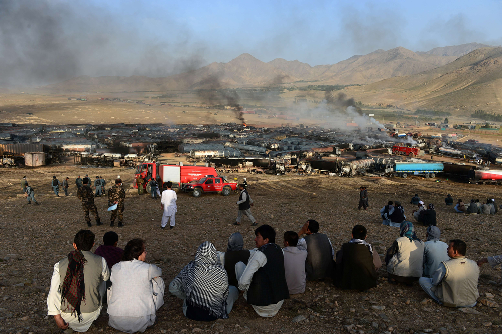 . Afghan residents watch as smoke rises from burning fuel trucks following an overnight attack by Taliban militants in Chawk-e-Arghandi on outskirts of Kabul on July 5, 2014. Taliban militants set fire to dozens of fuel trucks on the outskirt of Kabul, officials said. The fire triggered by a sticky bomb set a blaze dozens of fuel tankers waiting to enter the city in Chawk-e-Arghandi parking lot west of Afghan capital overnight. (WAKIL KOHSAR/AFP/Getty Images)