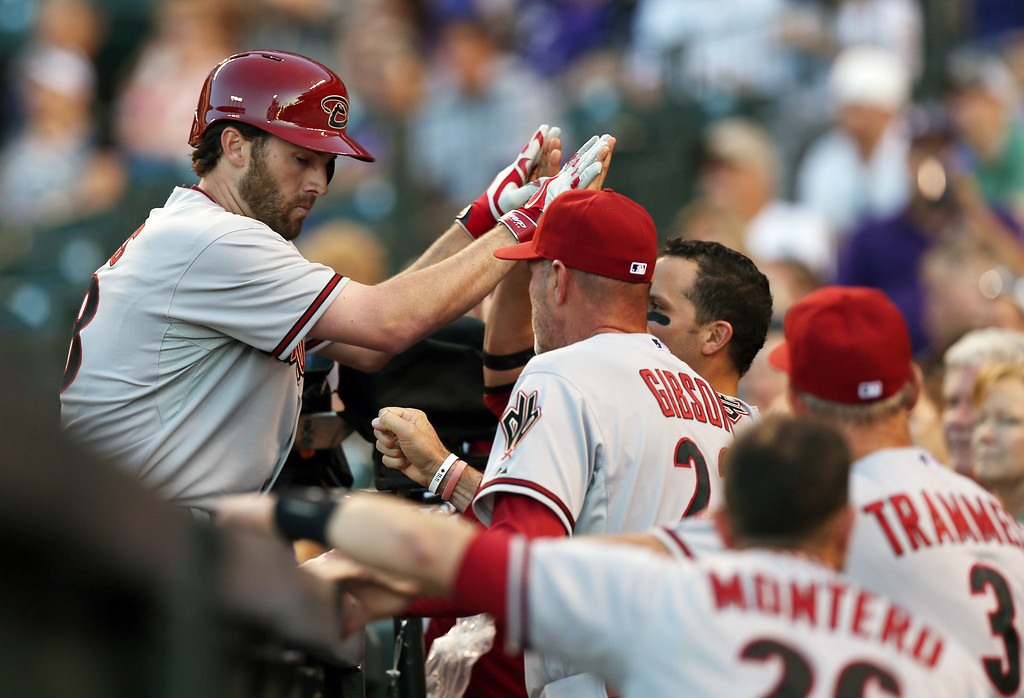 . Arizona Diamondbacks\' Nick Evans, left, is congratulated after hitting a solo home run by manager Kirk Gibson against the Colorado Rockies in the fourth inning of a baseball game in Denver on Tuesday, June 3, 2014. (AP Photo/David Zalubowski)