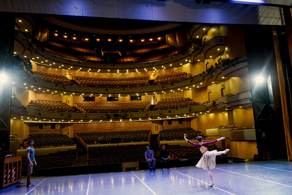 . In this Tuesday, Sept. 12, 2017 photo, ballet master Bruce Sansom, sitting center, give feedback to a dancer rehearsing for Romeo and Juliet in Montevideo, Uruguay. The director of Uruguay�s National ballet of the Sodre wants to turn the company in this small South American nation into one of the best in the world. (AP Photo/Matilde Campodonico)