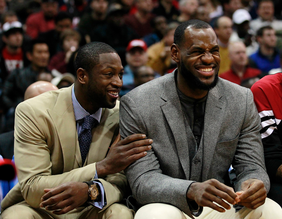 . Injured Miami Heat stars Dwyane Wade, left, and LeBron James react as a teammate scores in the second quarter of an NBA basketball game against the Atlanta Hawks in Atlanta on Thursday, Jan. 5, 2012. (AP Photo/John Bazemore)