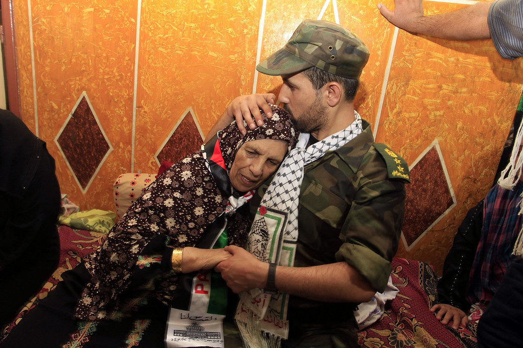 . Freed Palestinian prisoner Salah al-Sahair (R), who was held by Israel for 21 years, kisses his mother on the head following his return to the family home in Khan Younis in the southern Gaza Strip, early on August 14, 2013. Israel freed 26 Palestinian prisoners on August 14, hours before the two sides were to hold new direct peace talks amid a growing row over settlements.   SAID KHATIB/AFP/Getty Images