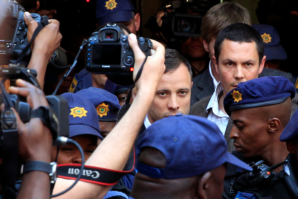 . Escorted by police and security, Oscar Pistorius leaves the court  in Pretoria, South Africa, Friday, Sept. 12, 2014. In passing judgement judge Thokozile Masipa  ruled out a murder conviction for the double-amputee Olympian in the shooting death of his girlfriend, Reeva Steenkamp,  but said he was negligent and convicted him of culpable homicide. Sentencing is scheduled for Oct. 13, 2014.  (AP Photo/Jerome Delay)