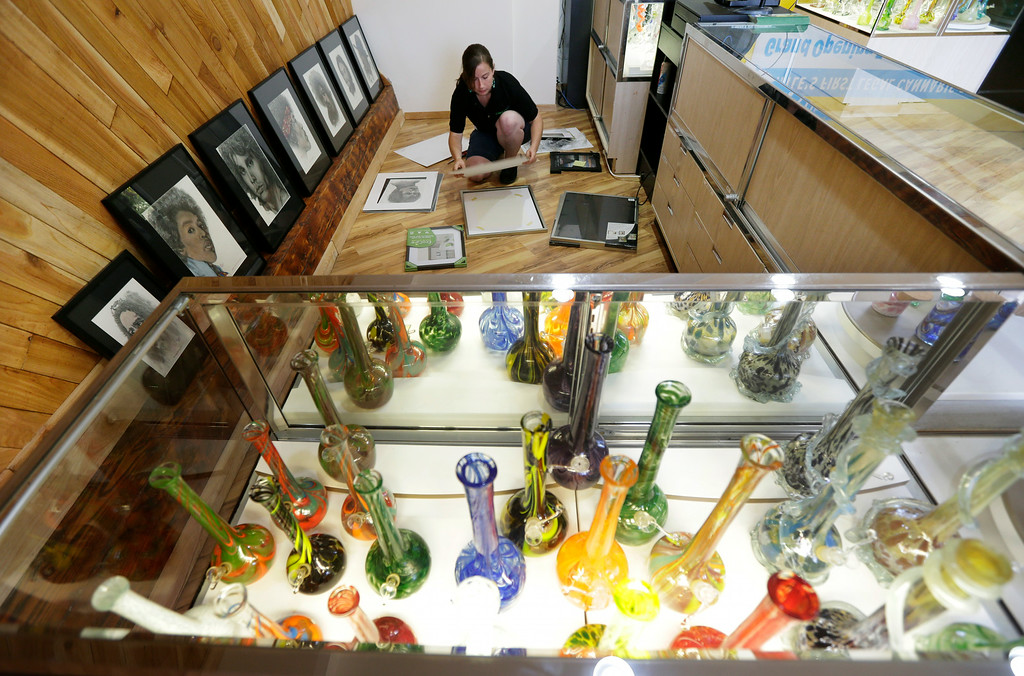 . Krystal Klacsan prepares artwork to be hung, Monday, July 7, 2014 behind a case displaying glass bongs at the recreational marijuana store Cannabis City in Seattle. (AP Photo/Ted S. Warren)