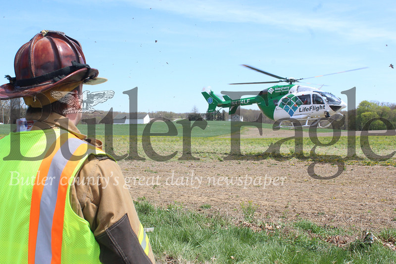 Harold Aughton/ Butler Eagle: A first responder watches as a victim of a head on collision is life flighted to the hospital. The accident occurred along Route 8 near Conquonessing Elementary School Tuesday afternoon, April 24.