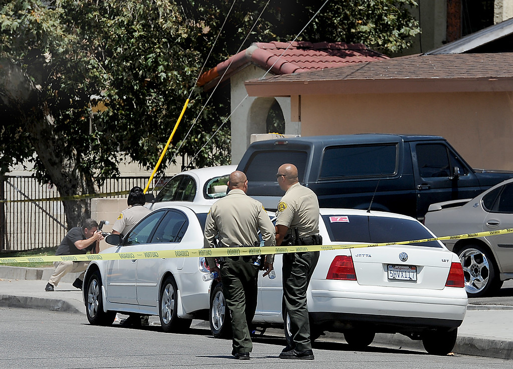 . Los Angeles County Sheriff\'s photographer, taking a picture of the crime scene where the shooting took place in the 10700 block of Weaver Avenue.    The wounded victim ran to the to the Weaver Park, a business complex where hed died of his gunshot wounds.  Los Angeles County sheriff\'s officials investigate a shooting at a business where a man is found dead 10700 block of Weaver Avenue in South El Monte on Tuesday, June 18, 2013. (SGVN/Staff photo by Walt Mancini)