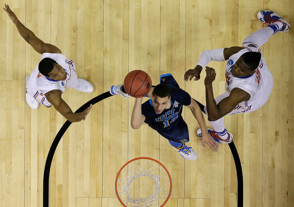 . UCLA guard Zach LaVine (14) shoots against Florida forward Will Yeguete, right and Florida Kasey Hill during the first half in a regional semifinal game at the NCAA college basketball tournament, Thursday, March 27, 2014, in Memphis, Tenn. (AP Photo/Mark Humphrey)