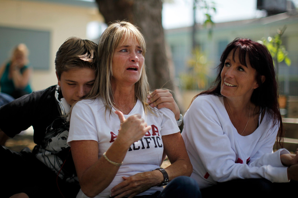 . Tammy Fah, 48, (C) is hugged by her son Matthew Stenger, 13, as she sits with  Kathy Jamieson, 43, (R) at Prototypes residential treatment program in Pomona, California, March 26, 2013. Prototypes is part of the Second Chance Women\'s Re-entry Court program, one of the first in the U.S. to focus on women. It offers a cost-saving alternative to prison for women who plead guilty to non-violent crimes and volunteer for treatment. Of the 297 women who have been through the court since 2007, 100 have graduated, and only 35 have been returned to state prison. Picture taken March 26, 2013. REUTERS/Lucy Nicholson