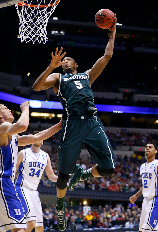 . Michigan State Spartans forward Adreian Payne (5) slam dunks past Duke Blue Devils forward Mason Plumlee (L), forward Ryan Kelly (34) and guard Quinn Cook during their Midwest Regional NCAA men\'s basketball game in Indianapolis, Indiana, March 29, 2013. REUTERS/Jeff Haynes